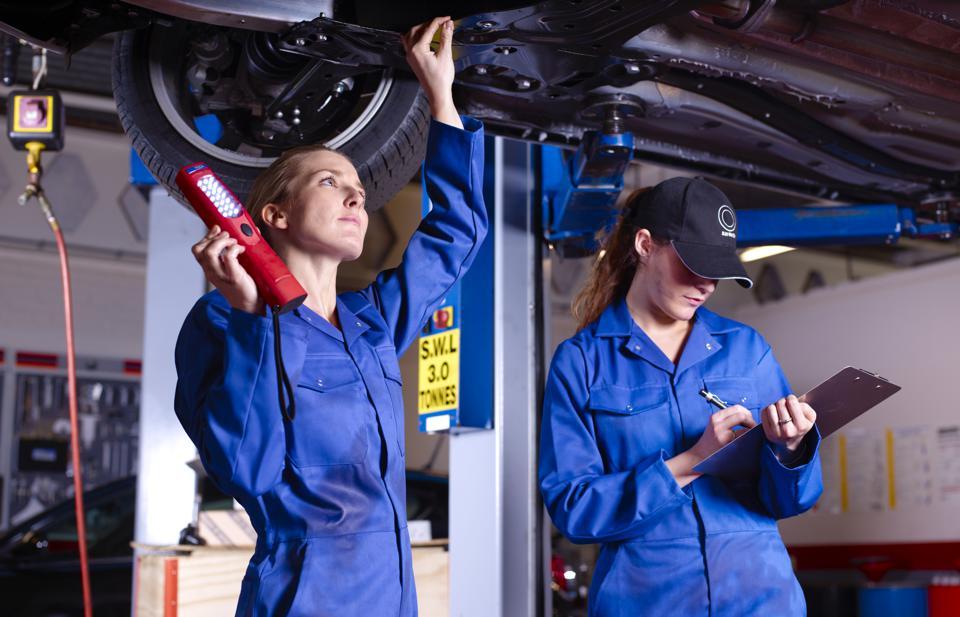 Female mechanics underneath car doing service