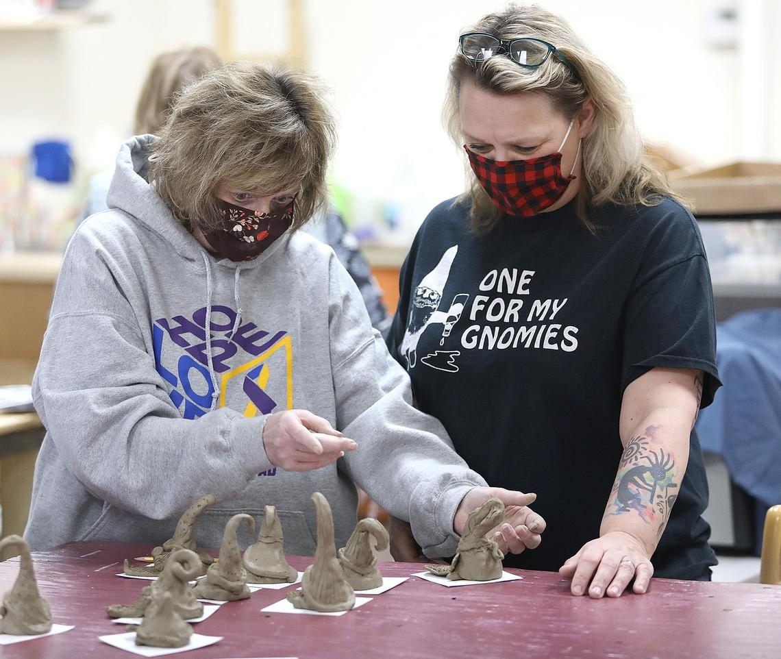 Michelle Foster, left, and Bridget Johnson look at their fellow classmates' first attempts at crafting gnomes out of clay during a class at CreativEdge Designs in Carlton Monday, Feb. 22.  (Jed Carlson / jcarlson@superiortelegram.com)