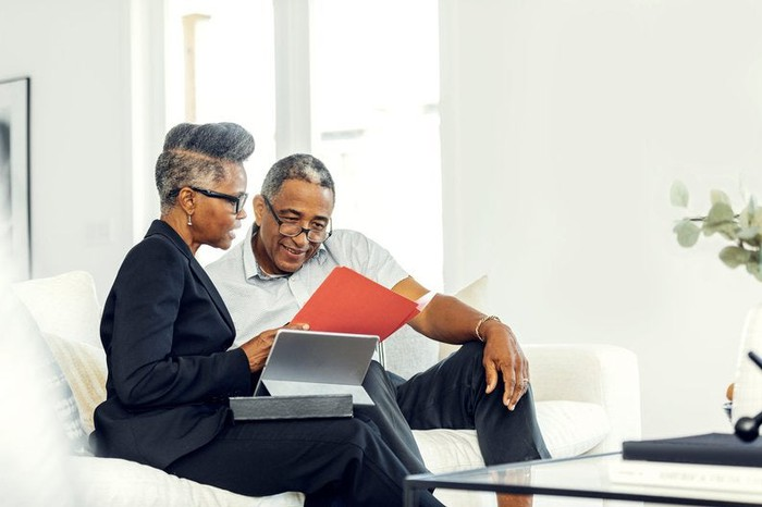 Two older adults discuss finances using a tablet on a couch.