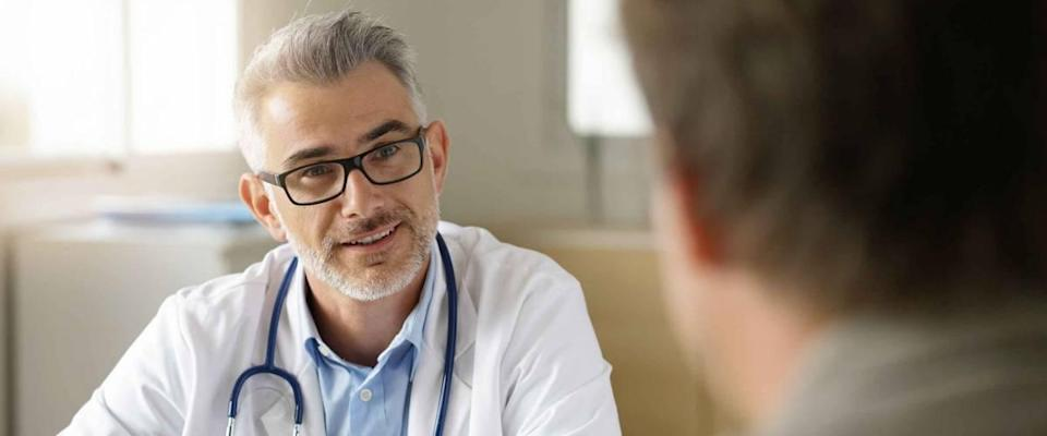Doctor talking to patient in office, patient's back to the camera.